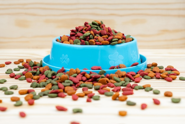 Pet bowl with dry food on wooden table