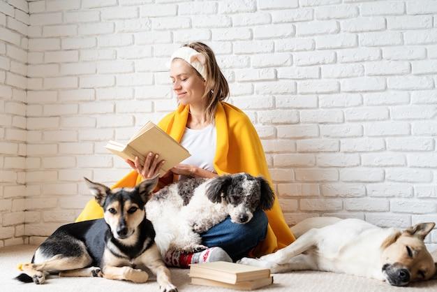 펫 케어. 책을 읽고 그녀의 강아지와 함께 앉아 노란색 격자 무늬에 재미 있은 웃는 젊은 여자