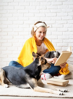 Pet care. funny smiling young woman in yellow plaid sitting with her dogs reading a book