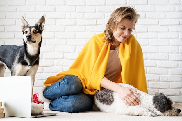 펫 케어. 그녀의 강아지와 함께 바닥에 앉아 노란색 격자 무늬에 재미있는 젊은 여자
