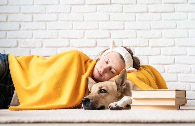 펫 케어. 노란색 격자 무늬 그녀의 강아지와 함께 자 고있는 재미있는 젊은 여자