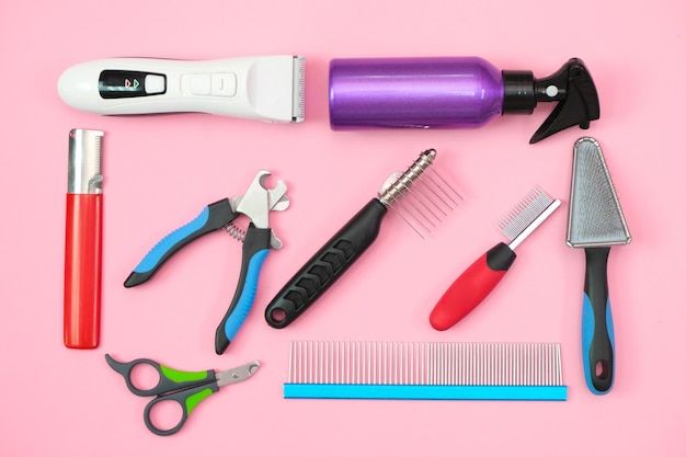 Pet care and grooming tools on a pink background. pet care and hygiene concept