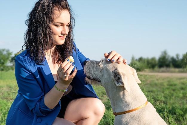 ペットの世話。ペットの採用。夏の晴れた日に公園で犬に餌をやる若い女性