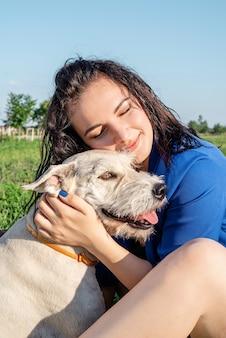 Уход за животными. усыновление домашних животных. молодая женщина играет и обнимает свою собаку в парке