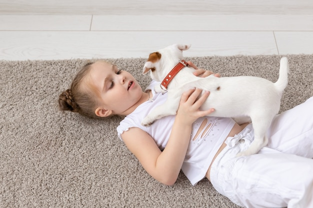Pet, childhood and animal concept - portrait of little child girl lying on the floor with puppy jack russell terrier.