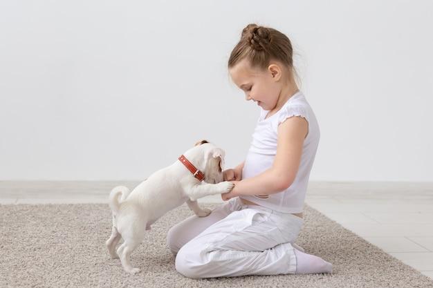 ペット、子供、動物のコンセプト-床に座って子犬に餌をやる魅力的な子供の女の子。