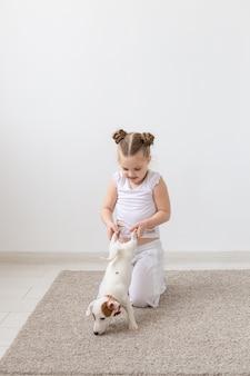 ペット、子供、動物の概念-足で子犬を保持している子供の女の子。