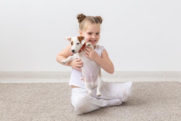 ペット、子供、動物のコンセプト-子犬ジャックラッセルテリアと一緒に座っている笑顔の子供の女の子。