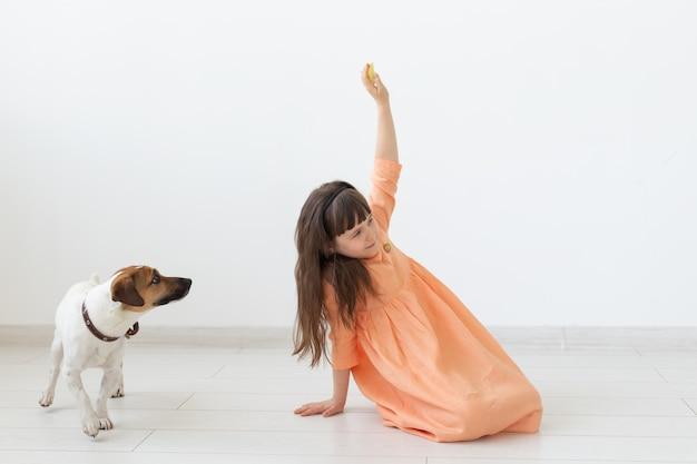 ペット、子供、犬のコンセプト-子犬と遊ぶドレスの少女