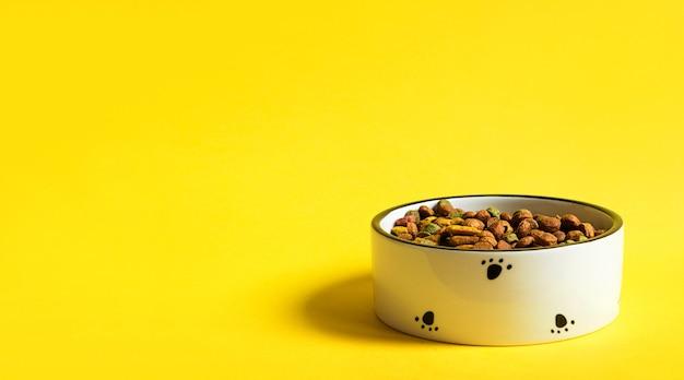黄色の背景に乾燥粒状食品とペットフードボウル。