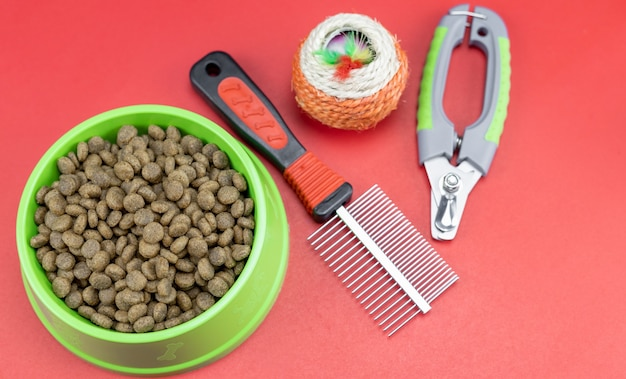 Pet food in bowls toy for pets on red background