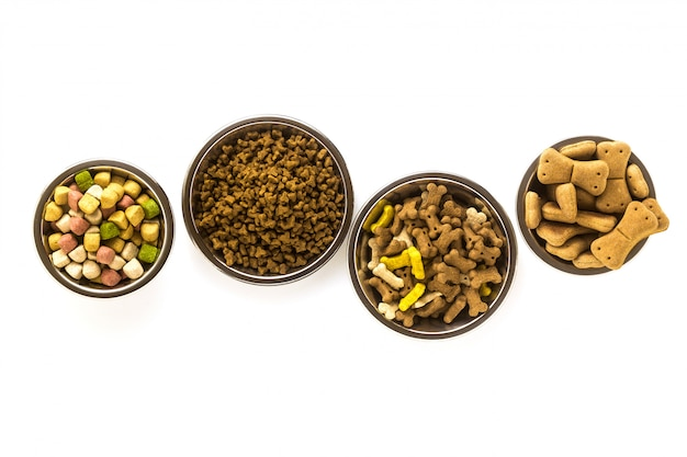 Pet food in bowls and toys isolated on white background