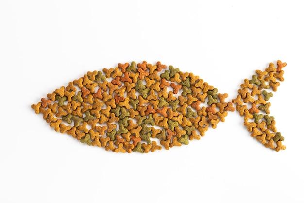 ペットフードは、白い背景の上に魚の形で配置されています。ペット、動物の餌やり。特別食、栄養トレーニング。上面図の背景。