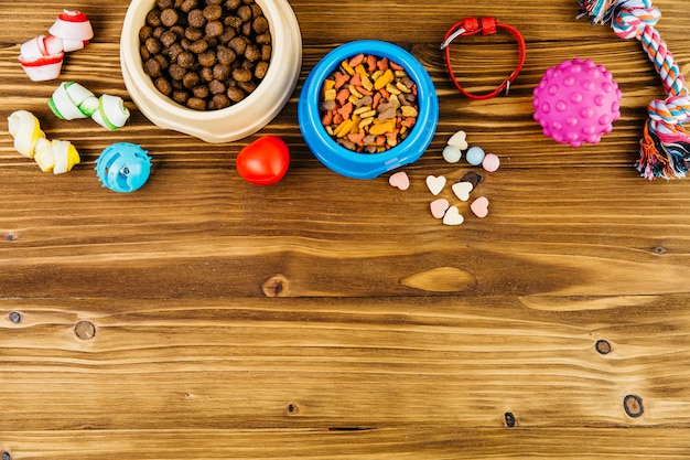 Pet food and toys on wooden surface