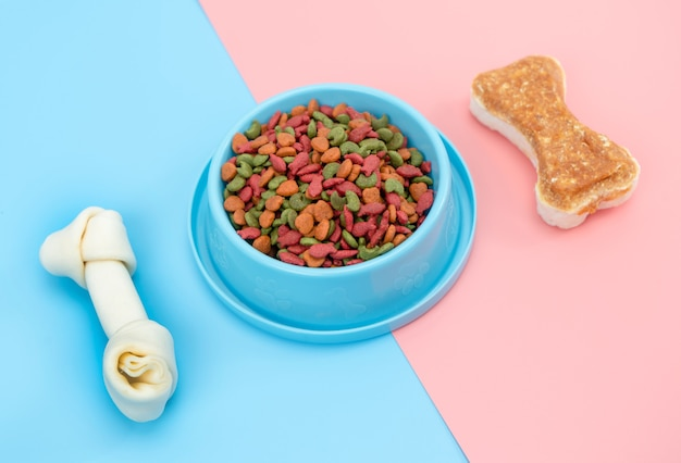 Pet food with snack bone for dog or cat on color surface