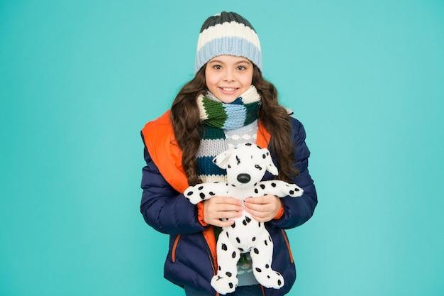 Идеи по сбору средств для домашних животных. прекрасный улыбающийся ребенок, дружелюбный с собакой. приют для животных. далматинская собака. счастливая малая улыбающаяся детская игра с мягкой собакой синим фоном. маленькая детская игрушка. концепция благотворительности.