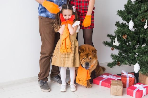Домашнее животное, праздники и праздничная концепция - крупный план семьи стоят возле елки.