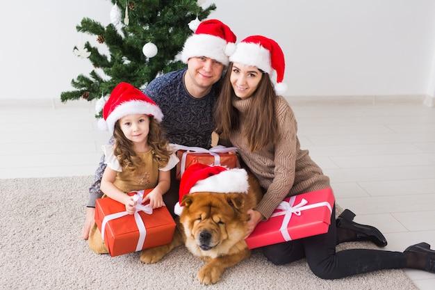 Домашнее животное, праздники и праздничная концепция - семья с собакой лежат на полу возле елки.