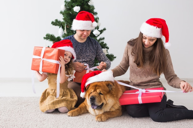 Pet, holidays and festive concept - family with dog are sitting on floor near christmas tree.