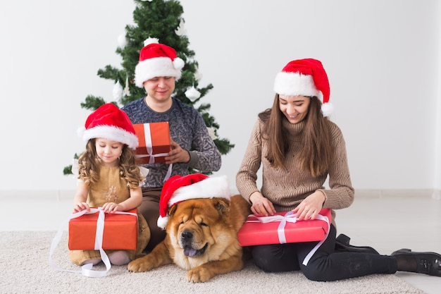 Pet, holidays and festive concept - family with dog are standing near christmas tree.