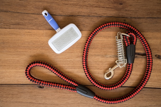 Pet leashes and brush on wooden background.