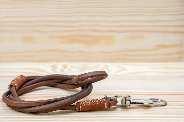 Кожаные поводки для домашних животных на деревянных фоне
