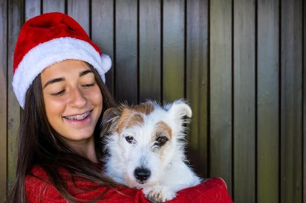 여자와 크리스마스에 애완 동물 사랑입니다. 행복한 순간, 크리스마스 모자를 쓴 웃는 얼굴. 인사와 기쁨.