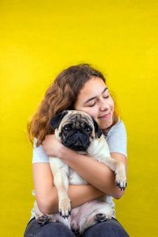 ペット愛。カーリーティーンエイジャーの女の子は愛で彼女の悲しいパグ犬を抱擁します。