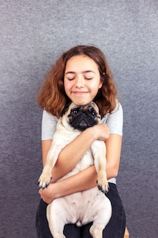 Pet love. curly teenager girl hugs her sad pug dog with love