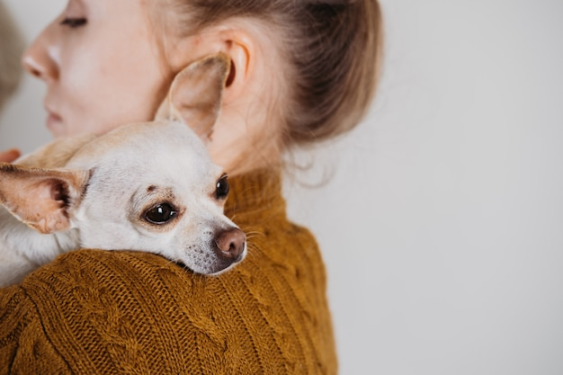 Pet love, homeless dog adoption, caring for a pet and animal concept. pet lovers, animal lovers. woman with new pet dog from shelter in her hands. puppy from shelter in new home.