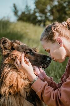 Любви любви. молодая довольно счастливая женщина играет с немецкой овчаркой