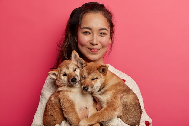 Pet lover and friendship with owner concept. asian woman plays with two pedigree small dogs, enjoys spending free time with domestic animals