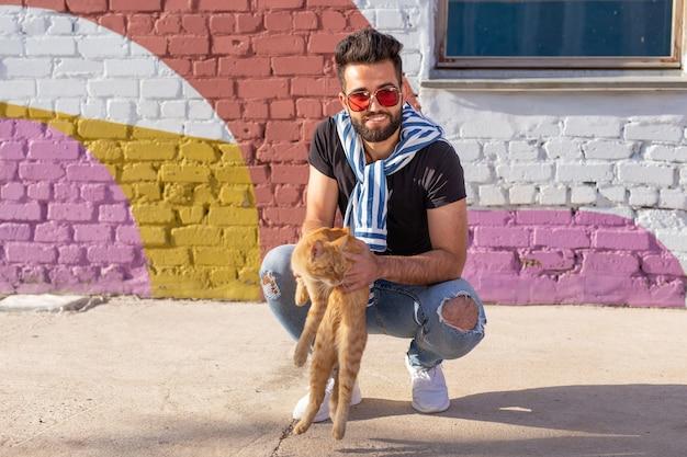애완 동물 소유자와 우정 개념-잘 생긴 아랍 남자는 귀여운 생강 고양이를 잡고 포옹합니다. 호기심 많은 표정으로 고양이