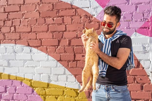 애완 동물 소유자와 우정 개념-잘 생긴 아랍 남자는 귀여운 생강 고양이를 잡고 포옹합니다. 호기심 많은 표정으로 고양이 프리미엄 사진