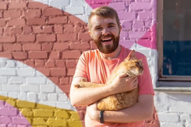 Владелец питомца и концепция дружбы - красивый мужчина держит и обнимает милую рыжую кошку. кот с любопытным выражением лица.