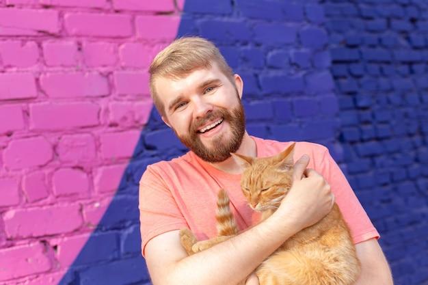 ペットの飼い主と友情の概念-ハンサムな男はかわいい生姜猫を抱きしめて抱きしめています。好奇心旺盛な表情の猫。