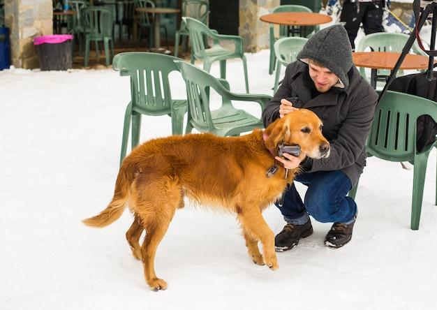 ペットの飼い主、犬、そして人々の概念-冬時間の屋外で若い笑顔の白人男性と犬。