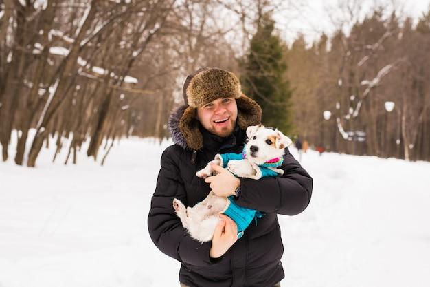 ペットの飼い主、犬、そして人々の概念-冬の時間に屋外でジャックラッセルテリアを保持している若い笑顔の白人男性。