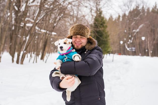 ペットの飼い主、犬、そして人々の概念-ジャックラッセルテリアを保持している若い笑顔の白人男性