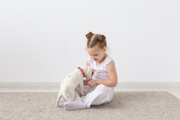 Pet's owner, children and dogs concept - little girl sitting on the floor with cute jack russell terrier puppy and playing