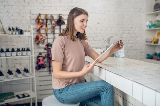 Зоомагазин. девушка в бежевой футболке сидит в зоомагазине и просматривает прайс-лист