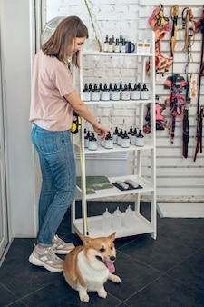 In a pet store. cute young girl with her dog spending time in a pet store