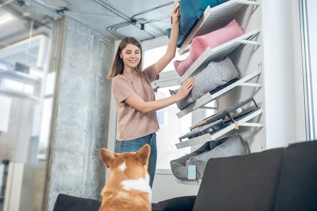 Зоомагазин. девушка в бежевой футболке выбирает кровать для своей собаки