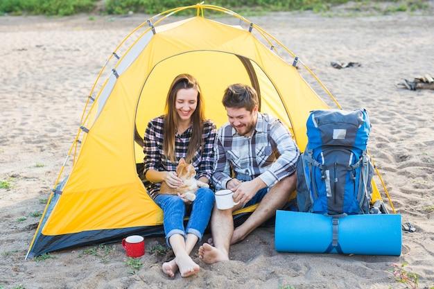 Домашнее животное, летний туризм и концепция природы - молодая пара, сидящая с кошкой возле палатки.