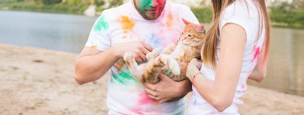 Домашнее животное, летний туризм, фестиваль холи и концепция природы - мужчина и женщина с кошкой на естественном фоне крупным планом