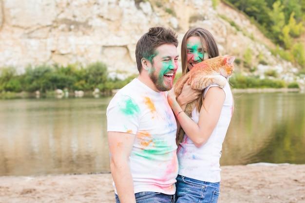 Домашнее животное, летний туризм, фестиваль холи и концепция природы - забавный мужчина и женщина с кошкой на естественном фоне.