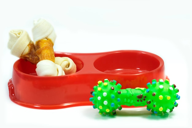 Pet supplies about snack bone in bowl with rubber toy isolated on white background