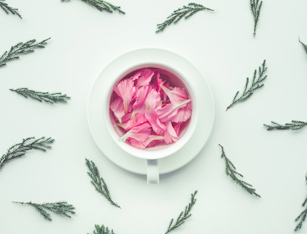 Цветок-лепесток в белой чашке с зелеными листьями.