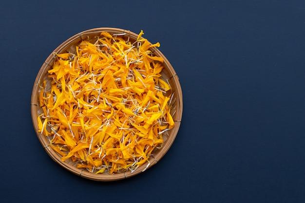 Petals of marigold flower on dark background.