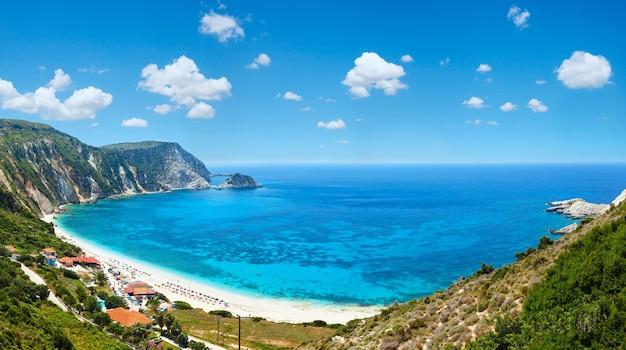 Летняя панорама пляжа петани (кефалония, греция). глубокое синее небо с кучевыми облаками. не всех людей узнают.